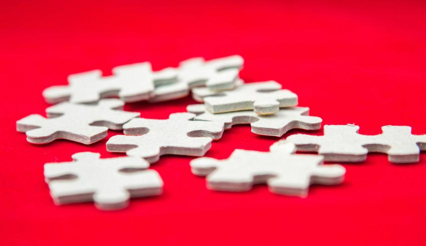 white puzzle pieces on red table mid tier law firm closing shop dibbsbarker joining dentons